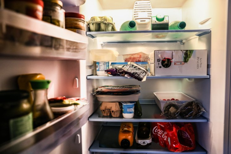refrigerator, open door, light, food, drinks, bottles, wine, coke, juice, eggs, yogurt, chocolate