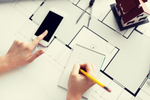 close-up-of-hands-with-blueprint-and-smarphone-pqhs97q