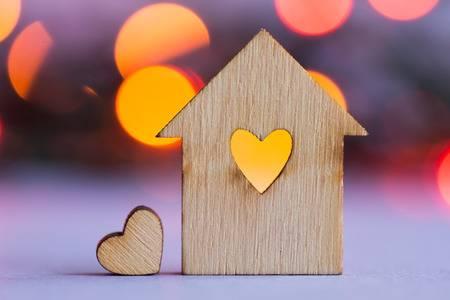 37916596-casa-de-madera-con-un-agujero-en-forma-de-corazc3b3n-con-poco-corazc3b3n-en-naranja-y-rojo-de-fondo-bokeh
